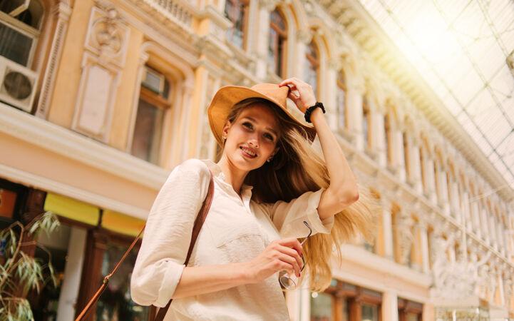 一个年轻的金发女游客戴着帽子的城市建筑肖像