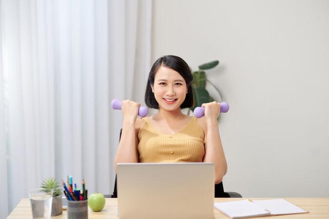 微笑的孕妇坐在椅子上 手里拿着两个哑铃 看着笔记本电脑