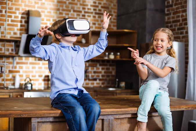 快乐的小男孩在测试虚拟现实设备 而他的妹妹在他身上束腰
