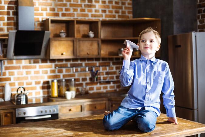 高兴的小男孩坐在厨房里玩纸飞机