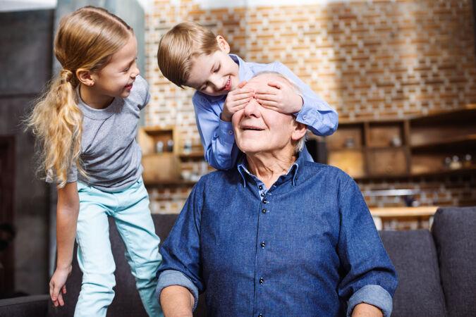 快乐的老人坐在沙发上 他的小孙子们闭上了眼睛
