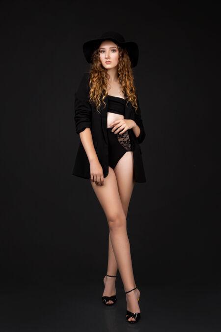 一个穿着内衣 夹克和帽子在黑墙上摆姿势的女人