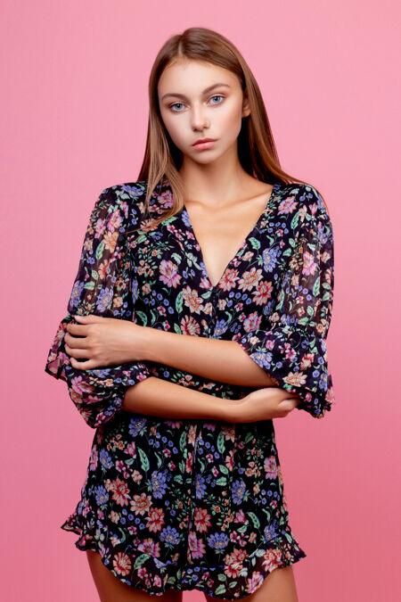 穿着工作服的时尚年轻女子在粉红色的墙上摆姿势