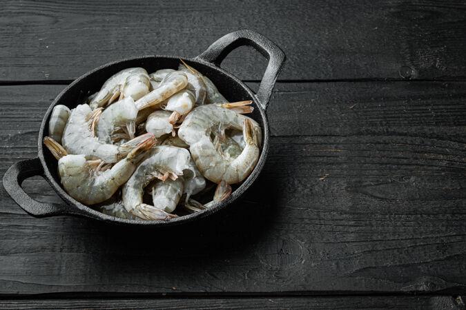 虎虾或亚洲虎虾 装在铸铁煎锅里 放在黑木桌上 有复印空间