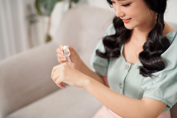 美丽的年轻女子正在用保湿抗衰老血清治疗她的手