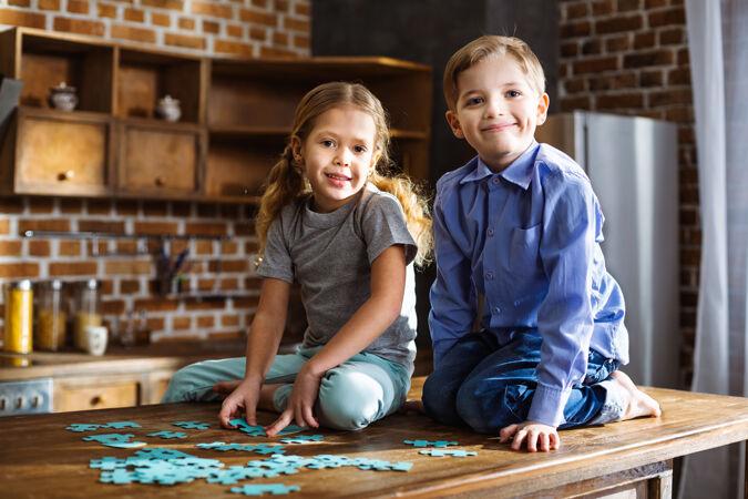 快乐的小兄弟姐妹坐在厨房里拼拼图