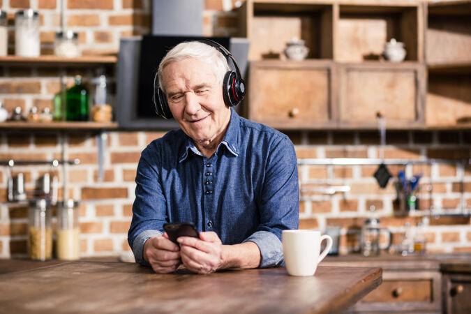快乐的老人一边用他的智能手机一边听音乐