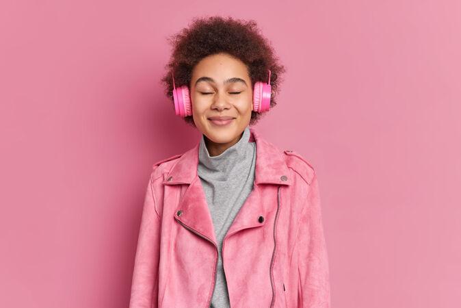 快乐的年轻非洲裔美国妇女的工作室拍摄享受愉快的旋律闭上眼睛通过耳机听音乐