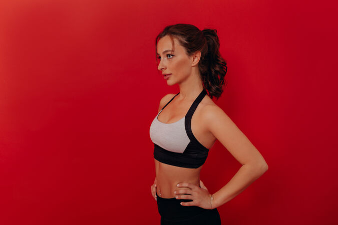 美丽的黑发女子身穿运动上衣的特写肖像画被隔离在红墙上