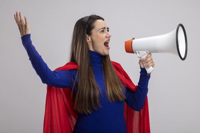 快乐的年轻超级英雄女孩看着一边用扩音器说话一边举起手隔离在白色背景上