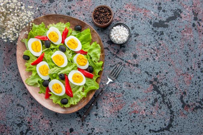 顶视图美味的鸡蛋沙拉与绿色沙拉和橄榄在轻背景