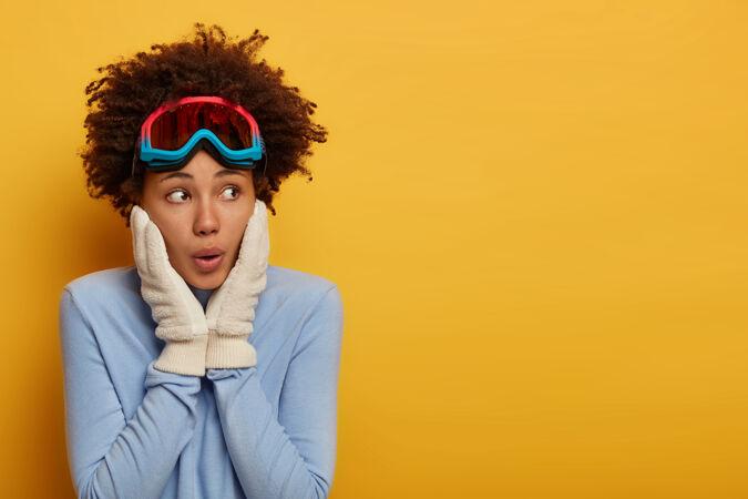 给人印象深刻的卷发女孩双手放在脸颊上 神色出奇地放在一边 穿着舒适的蓝色套头衫