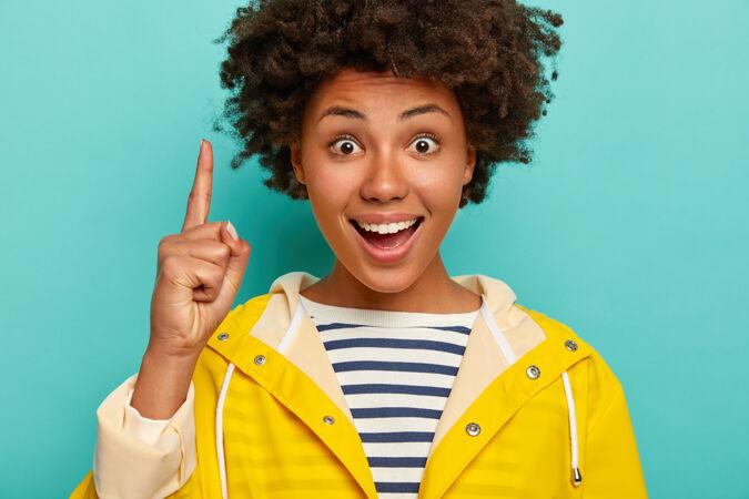 有趣快乐的非洲女孩 卷曲的黑发 食指向上 展示了上面的东西 睁大了眼睛