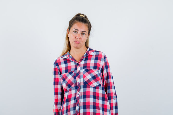 穿着格子衬衫的年轻女士看着摄像机 看起来很无助前视图