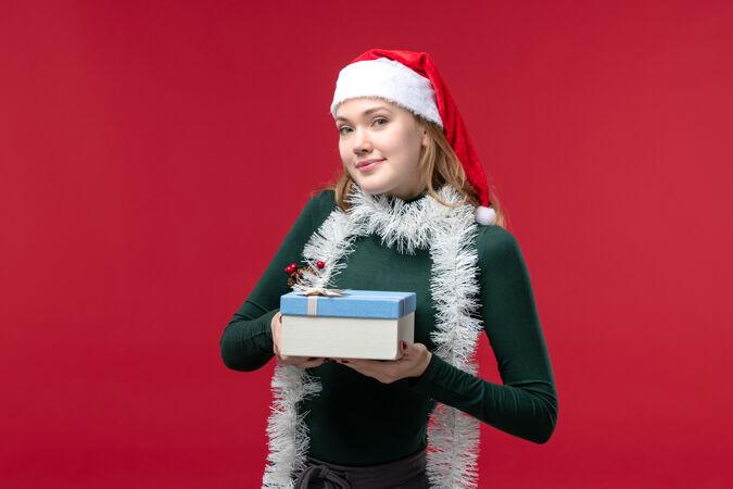 正面图红色背景上手持新年礼物的年轻女子