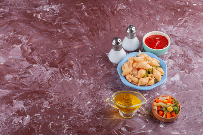 意大利贝壳面食配番茄酱和混合蔬菜沙拉 放在浅色桌上