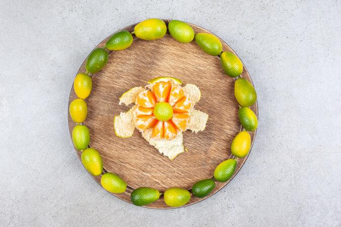 木板上有一堆金橘的去皮橘子俯视图