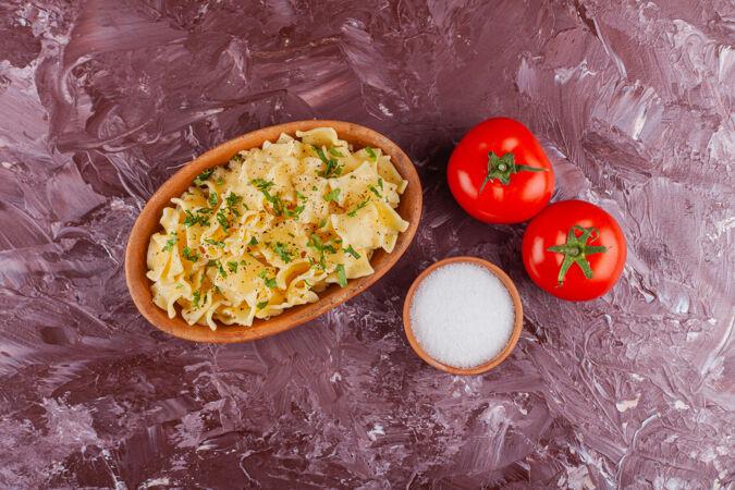 淡桌上放着蛋黄酱和新鲜的红色西红柿的潘恩意大利面
