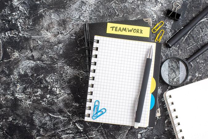 顶视图团队合作笔记附在黑色记事本上 背景为黑色