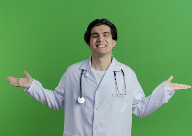 面带微笑的年轻男医生穿着医用长袍和听诊器 双手空空 双眼紧闭 隔离在绿色的墙上