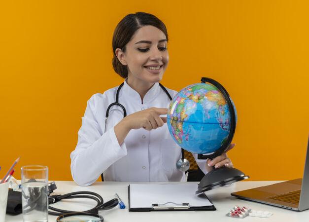 面带微笑的年轻女医生穿着医用长袍和听诊器坐在办公桌旁 拿着医疗工具和笔记本电脑 看着并用手指着隔离在黄色墙上的地球仪