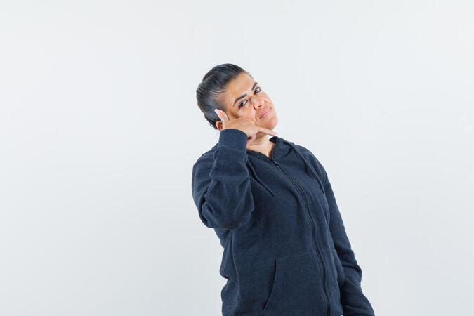 一个黑发女人穿着夹克 露出打电话的姿势 看上去很高兴
