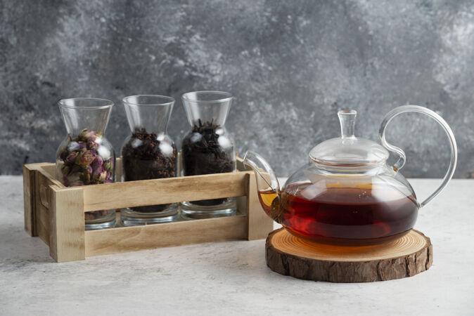 在木板上放着茶的玻璃茶壶