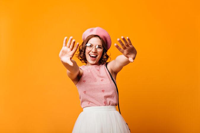 戴着贝雷帽的快乐白人女孩对着镜头笑着挥手黄色背景下漂亮年轻女子摆姿势的摄影棚照片