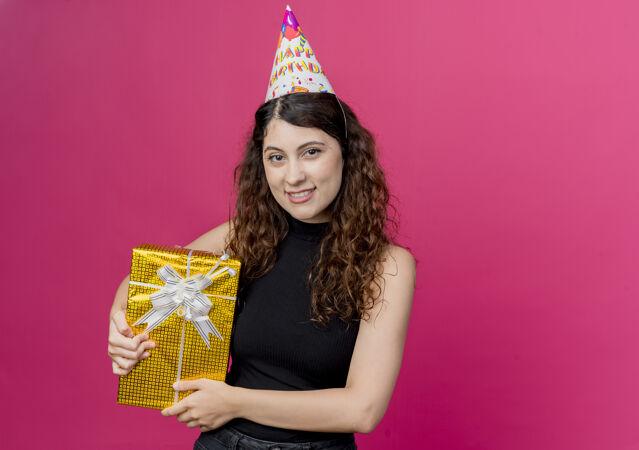 一位年轻漂亮的女士 卷发 戴着节日帽 手里拿着生日礼盒 脸上洋溢着欢笑 生日派对的概念是粉色的