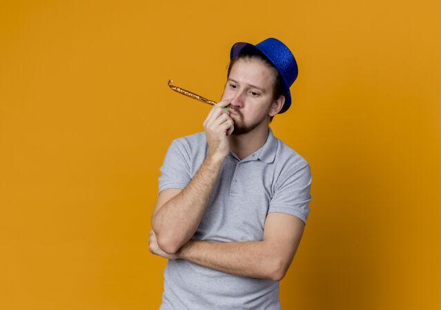 戴着帽子的困惑的年轻人在庆祝生日派对上带着悲伤的表情越过橘子